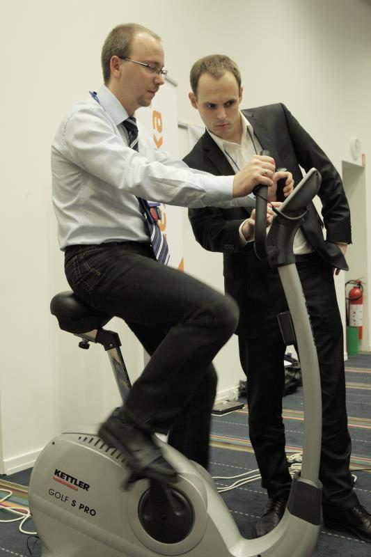 Dvaja muži vedľa stacionárneho bicykla