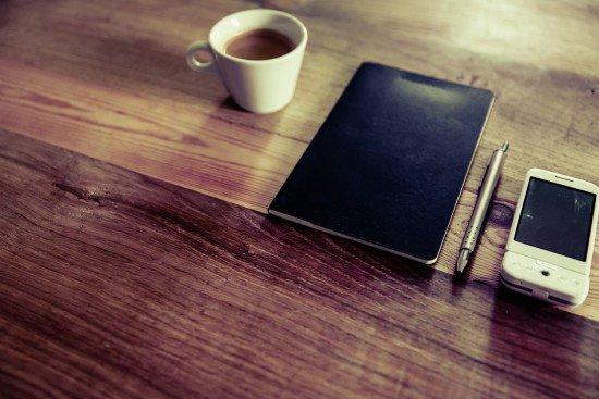 Šálka kávy, zápisník, pero a mobil na stole