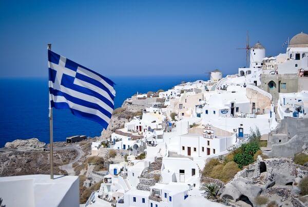 Grécka vlajka v pozadí s mestečkom