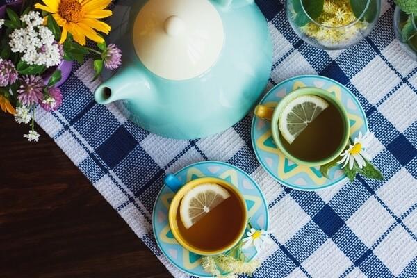 Čajník a šálky s čajom s kvetinovou dekoráciou